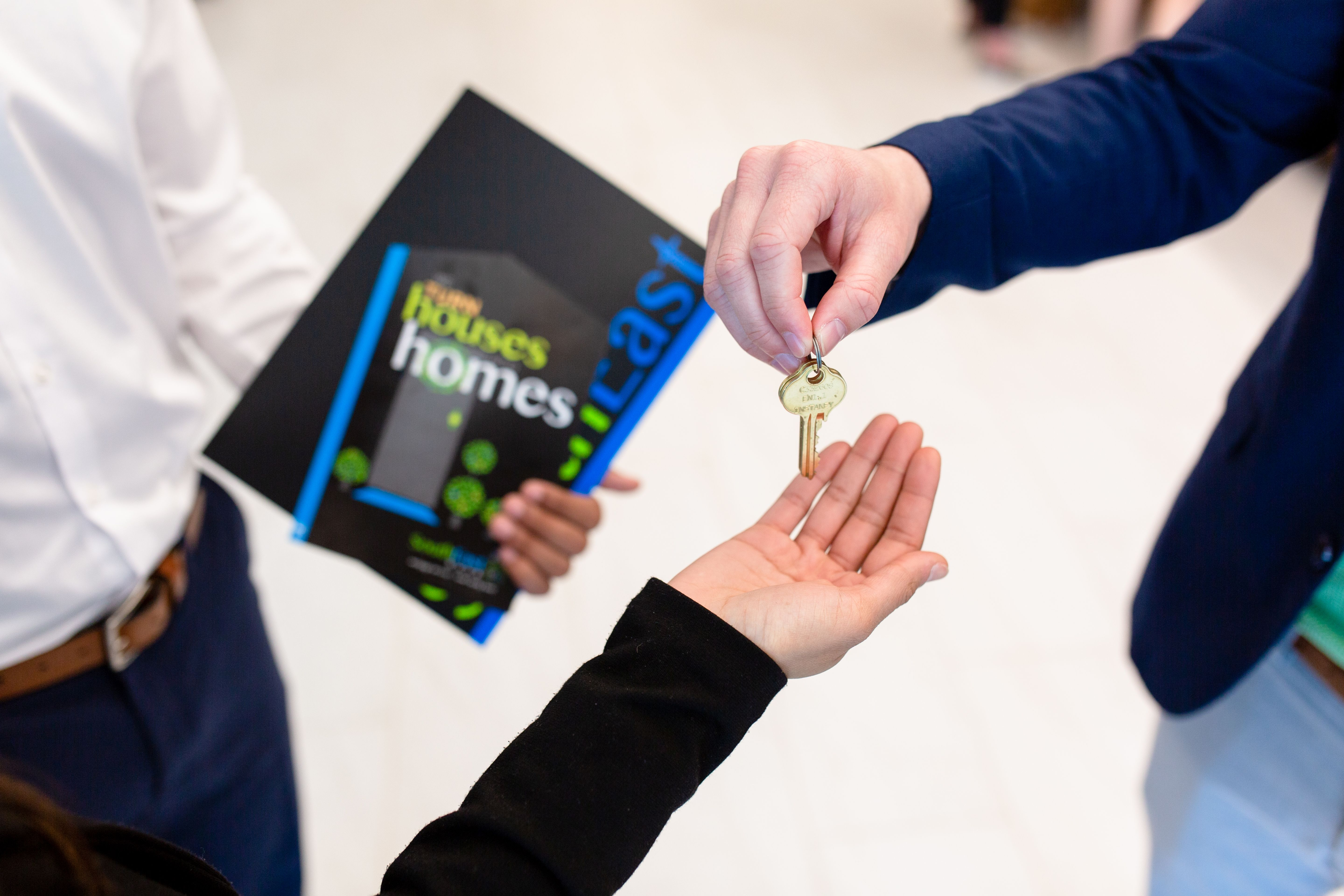 SouthEast Bank employee handing family keys to their new home